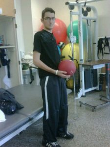 Image of Nicholas Morihovits at rehab bouncing the ball and standing on his own