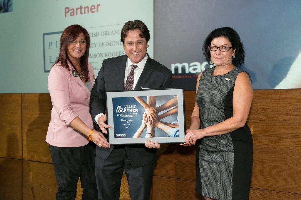 Thomson Rogers' Ian Furlong, on behalf of PIA Law, accepts an award in recognition of PIA Law's support of MADD Canada
