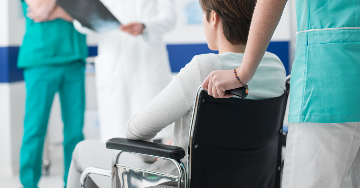 woman being pushed in a wheelchair by an attendant care worker